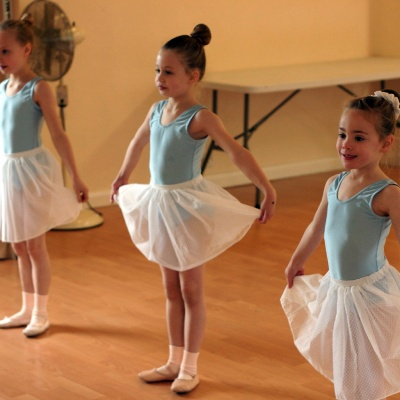 Three girls standing in 1st position in ballet class wearing uniform leotards and skirts