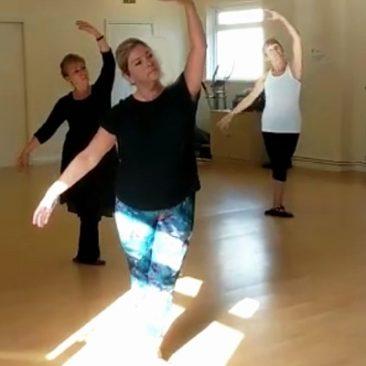 Three women performing port de bras in ballet class