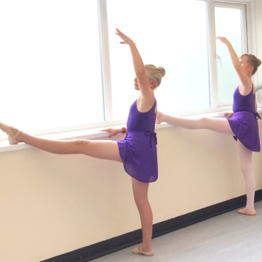 Image showing two young dancers limbering in ballet uniform