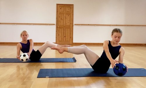 two dancers executing a mat based exercise