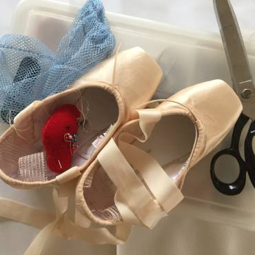 image showing a pair of pointe shoes with sewing kit